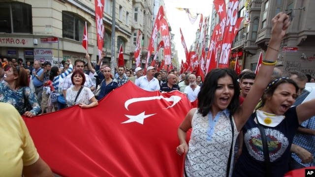 Protesters shout slogans as they hold a Turkish flag during the third day of nationwide anti-government protest at the Taksim square in Istanbul, June 2, 2013.