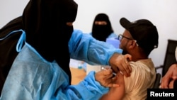 FILE - A man receives the AstraZeneca vaccine against COVID-19 at a medical center in Taiz, Yemen, April 23, 2021.