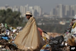 In this May 12, 2014 photo, Divan Rosa carries a bag loaded with recyclable trash as he works inside the Estrutual landfill in Brasilia, Brazil.