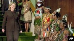 U.S. Secretary of State Hillary Rodham Clinton walks past a group of girls in traditional dress after a meeting with Papua New Guinea Prime Minister Michael Somare on Wednesday, Nov. 3, 2010 in Port Moresby, Papua New Guinea.