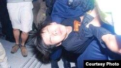 香港学民思潮召集人黄之锋在民主示威期间被胡椒喷雾喷中倒地,被警员铐手铐抬走。(资料照,2014年9月26日 张洁平微信图片)