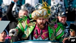 In this Feb. 8, 2018, file photo, Philadelphia Eagles center Jason Kelce, wearing a Mummers costume, speaks at the conclusion of the NFL team's Super Bowl victory parade in front of the Philadelphia Museum of Art in Philadelphia. (AP Photo/Alex Brandon)