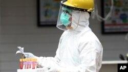 Seorang petugas kesehatan membawa sampel darah saat tes cepat virus corona di sebuah rumah sakit di Jakarta, 28 April 2020. (Foto: AP))