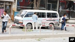 Journalists stand near a bullet-ridden mini-van during an on-going attack in Kabul on September 13, 2011.