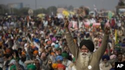 An elderly farmer shouts slogans as others listen to a speaker as they block a major highway during a protest to abolish new farming laws they say will result in exploitation by corporations. (AP Photo/Altaf Qadri)