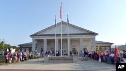 A gathering of same sex marriage supporters, left, and supporters of Rowan County Clerk Kim Davis, right, face off in front of the Rowan County Courthouse in Morehead, Ky., Sept. 1, 2015.