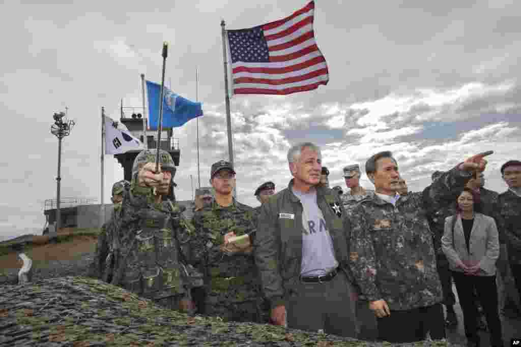 방한 중인 척 헤이글 미국 국방장관(가운데)이 30일 비무장지대를 방문한 가운데, 동행한 김관진 한국 국방장관(가운데 오른쪽)이 북측 지역을 가리키고 있다.