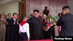 지난 10일 평양에서 열린 군중대회에서 김여정 노동당 선전선동부 부부장(붉은 원)이 주석단 위의 김정은 노동당 위원장에게 축하 꽃다발을 챙겨주고 있다. 조선중앙TV 영상 캡처.