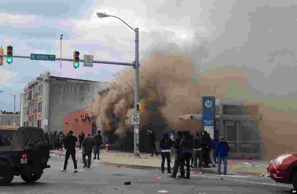 El humo sale de una farmacia CVS incendiada por los manifestantes.