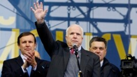 U.S. Senator John McCain (C) waves to pro-European intergration protesters during a mass rally at Independence Square in Kyiv December 15, 2013. Flanking hi, are U.S. Senator Chris Murphy (L) and one of Ukraine's opposition leaders, Oleh Tyahnybok.