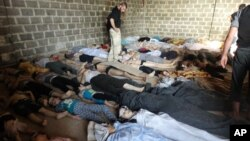 FILE - A photo taken on August 22, 2013, purports to show some of the estimated 1,000 victims of a suspected chemical weapons attack in the Damascus suburb of East Ghouta, Syria.