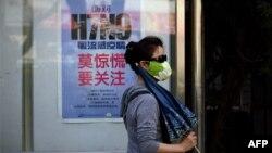 Phụ nữ đeo mặt nạ đi ngang một áp phích hướng dẫn cách làm thế nào để tránh virus cúm gia cầm H7N9 trên đường phố ở Bắc Kinh.
