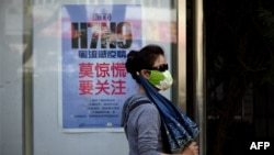 A woman wears a face mask as she walks past a poster showing how to avoid the H7N9 avian influenza virus, by a road in Beijing, April 24, 2013.