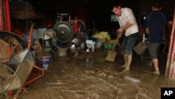 Taiwanese people scrape the mud off their house following flood and landslides triggered by typhoon Nanmadol in Laiyi, Pingtung County, Southern Taiwan, Monday, Aug. 29, 2011. Nanmadol slammed into Taiwan, closing schools, workplaces and government office