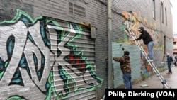 Members of Art Bloc DC and 2DK work on a graffiti mural in U Street.