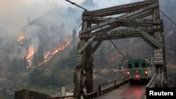 The TePee wildfire is seen burning at the Manning Bridge as it crosses the Salmon River near Riggins, Idaho, in this U.S. Forest Service picture taken Aug. 29, 2015.