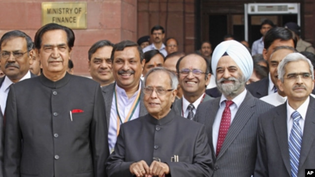 India's Finance Minister Pranab Mukherjee poses as he leaves his office to present the 2012/13 federal budget in New Delhi, March 16, 2012.