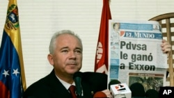 "FILE - Venezuela's Oil Minister Rafael Ramirez shows to the media in Caracas a newspaper, which reads in Spanish ""PDVSA defeats Exxon""."