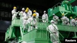 Giới truyền thông và nhân viên TEPCO trong trang phục bảo hộ bước xuống máy xử lý nhiên liệu trong tòa nhà của lò phản ứng số 4 tại nhà máy Fukushima Daiichi