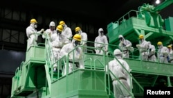 FILE - Members of the media and Tokyo Electric Power Co. (TEPCO) employees walk down the steps of a fuel handling machine on the spent fuel pool inside the No. 4 reactor building at the Fukushima Daiichi nuclear power plant in Fukushima prefecture, November 7, 2013.