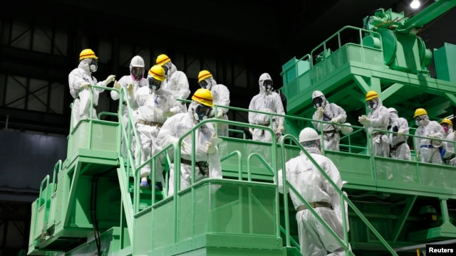 Members of the media and Tokyo Electric Power Co. (TEPCO) employees wearing protective suits and masks walk down the steps of a fuel handling machine on the spent fuel pool inside the No.4 reactor building at the tsunami-crippled TEPCO's Fukushima Daiichi