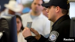 FILE - A U.S. Customs and Border Protection officer checks a passport at a border crossing in San Ysidro, California, Jan. 31, 2008. A firm commissioned by U.S. Secretary of State Rex Tillerson recommends that passport and visa issuance be transferred from the State Department to the Department of Homeland Security.
