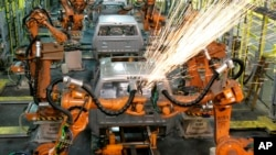 In this Sept. 12, 2008 file photo, assembly line robots weld the front cab of a Chrysler pickup truck being assembled in Warren, Michigan.