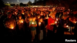 People hold candles during a memorial service for Charleston Hartfield, an off-duty Las Vegas police officer who was killed during the mass shooting, in Las Vegas, Nevada, Oct. 5, 2017.