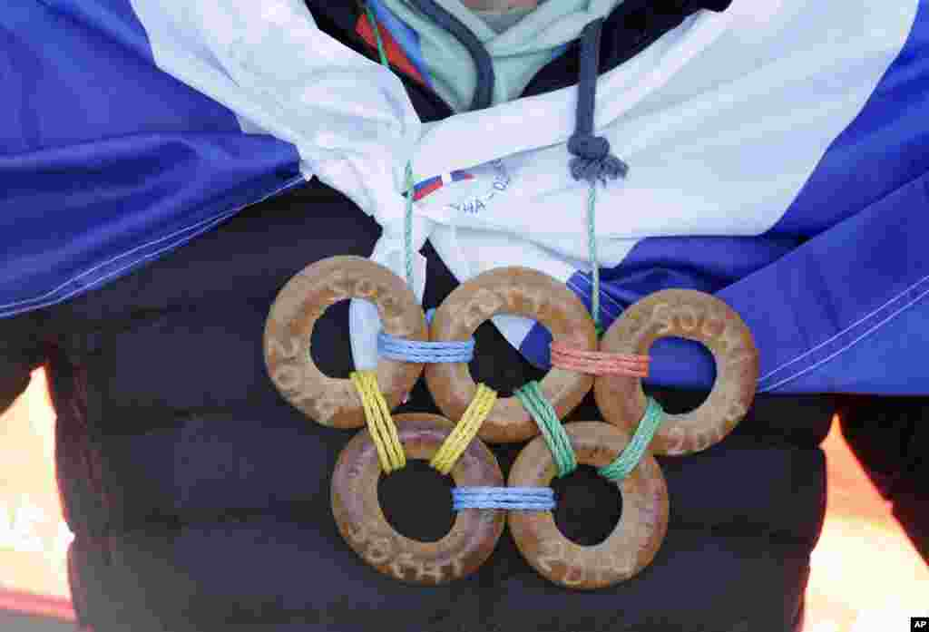 A spectator wears the Olympic rings made from bagels during the men's ski slopestyle qualifying at the Rosa Khutor Extreme Park, at the 2014 Winter Olympics, Feb. 13, 2014.
