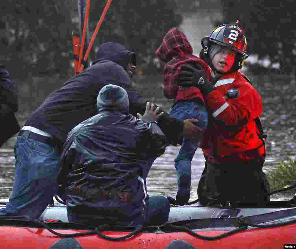 Residents, including a young child, are rescued by emergency personnel from flood waters brought on by Hurricane Sandy in Little Ferry, New Jersey, October 30, 2012.