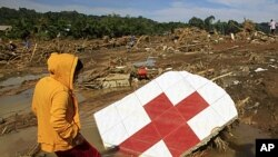 A woman stands next to a Red Cross sign among debris in a village hit by flashfloods brought by Typhoon Washi in Cagayan de Oro, southern Philippines, December 18, 2011.