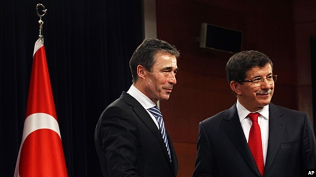 Secretary-General of NATO Anders Fogh Rasmussen, left, and Turkey's Foreign Minister Ahmet Davutoglu shake hands after a joint news conference in Ankara, Turkey, February 17, 2012.