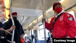 Jose Medina (left) and Chris Carbonell (right) patrols on the 7 train in New York City. (Photo by Janine Phakdeetham)