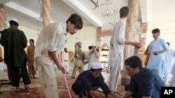 星期五巴基斯坦工作人員清理遭到自殺炸彈爆炸的清真寺的地板
