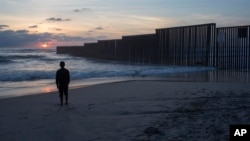 A man who gave his name as Hugo stands on the shore of the Pacific Ocean as his friend films him, backdropped by the U.S.-Mexico border fence that separates Tijuana, Mexico, from San Diego, California, April 4, 2017.