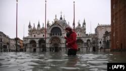 "Seorang wanita melintasi alun-alun St. Mark yang dibanjiri oleh Basilika Santo Markus setelah ketinggian air pasang semalam ""Alta Acqua"", awal 13 November 2019 di Venesia. (Foto: AFP)"