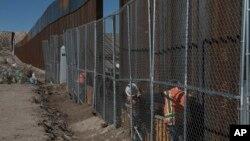 Công nhân tiếp tục công việc lắp đặt một hàng rào cao ở biên giới Mexico-Mỹ chia cách thị trấn Anapra của Mexico và Sunland Park của Mỹ ở New Mexico, 25/1/2017.