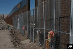 Workers continue work raising a taller fence in the Mexico-US border separating the towns of Anapra, Mexico and Sunland Park, New Mexico, with funding from a 2006 law.