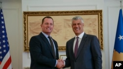FILE - Kosovo President Hashim Thaci, right, shakes hands with U.S. special envoy for the Kosovo-Serbia dialogue, Ambassador Richard Grenell, in Kosovo's capital of Pristina, Oct. 9, 2019.