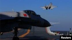중국 군이 지난해 12월 보하이 해에서 실시한 실탄사격훈련에서 항공모함 탑재 전투기들이 이륙하고 있다.