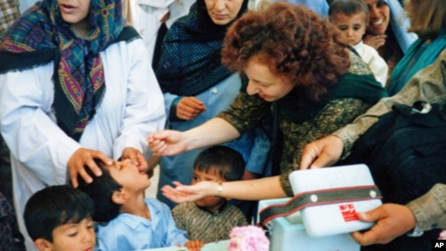FILE - Ellyn Ogden, USAID's worldwide polio eradication coordinator, immunizes a child during a festive kick-off event for a polio vaccination campaign in Kabul, Afghanistan.