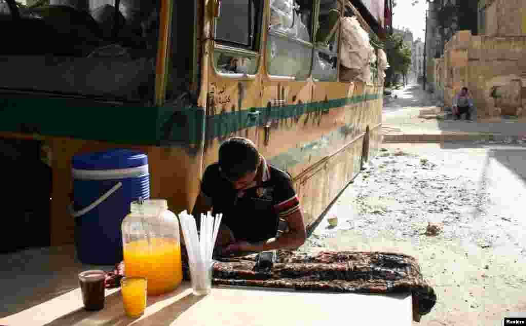 A boy sells juice near a damaged bus in Aleppo's Bustan al-Qasr neighborhood, May 30, 2013.
