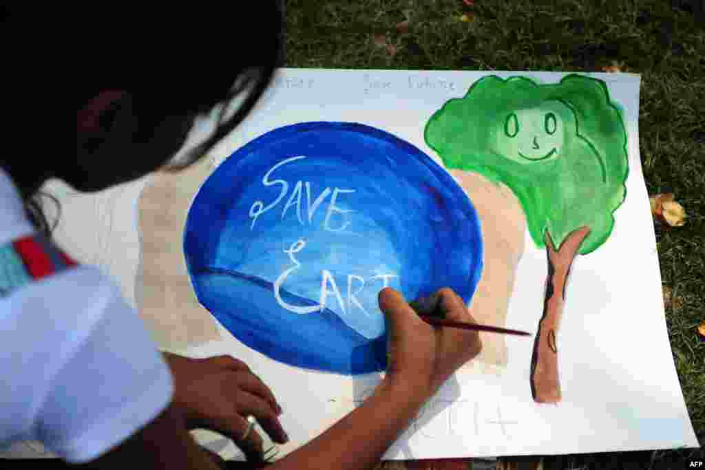 An Indian child paints during an awareness event organized by the Aakalpan Artist Society commemorating Earth Day in Allahabad, April 22, 2013.