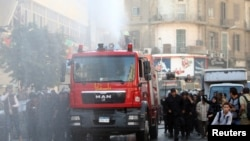 Riot police fire a water cannon to disperse people protesting against a new law restricting demonstrations, in downtown Cairo, Nov. 26, 2013.
