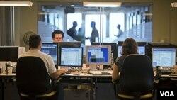 Para pialang di Tel Aviv mencermati pergerakan nilai saham di bursa, Minggu (7/8).