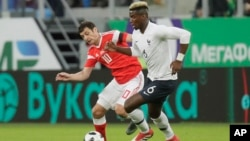 France's Paul Pogba, right, and Russia's Fyodor Smolov during the international friendly soccer match between Russia and France in St.Petersburg, Russia, Tuesday, March 27, 2018. (AP Photo/Dmitri Lovetsky)