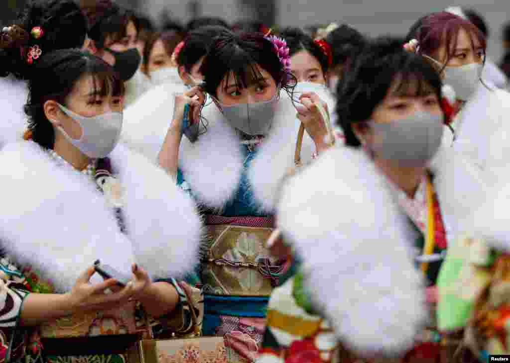 Kimono-clad youth wearing protective face masks leave their Coming of Age Day celebration ceremony at Yokohama Arena in Yokohama, south of Tokyo, Japan, during the government declared the second state of emergency for the capital and some prefectures, amid the COVID-19 pandemic.