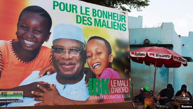 "Women sell food in front of a poster for presidential candidate Ibrahim Boubacar Keita in Bamako, July 16, 2013. The poster reads, ""For the happiness of Mali."""