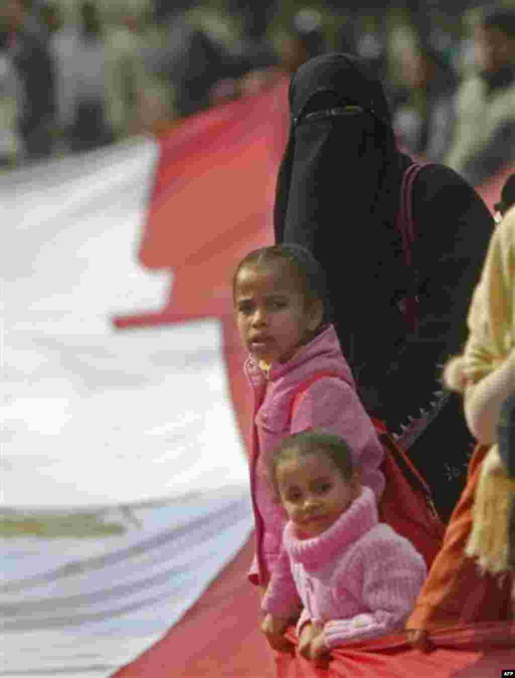 An Egyptian protester and her childern wave a giant Egyptian flag in front of the Egyptian Parliament in Cairo, Egypt, Wednesday, Feb. 9, 2011. Around 2,000 protesters waved huge flags outside the parliament, located several blocks from Tahrir Square, whe