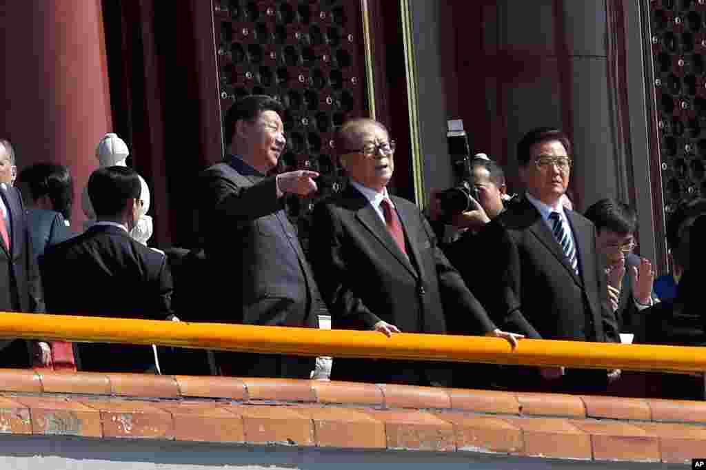 """在""""纪念中国人民抗日战争暨世界反法西斯战争胜利70周年""""阅兵时,中国主席习近平和前主席江泽民交谈。胡锦涛在旁边(2015年9月3日)。不久前江泽民两次被中国官媒提到,是在为去世高官钱其琛和布赫送花圈者的名单中。在这之前,在2017年春节前夕""""习近平等党和国家领导人分别看望或委托有关方面负责同志看望""""的许多人里,江泽民名列第一位。但这都是""""只见名字不见人""""。"""